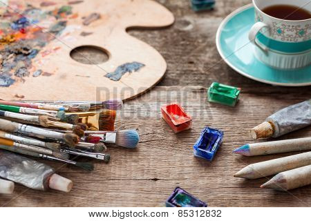 Paintbrushes, Artist Palette, Pencils, Coffee Cup, Watercolor And Oil Paints On Desk In Painter Stud