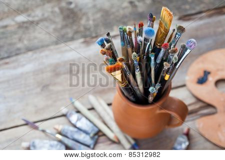 Paintbrushes In A Jug From Potters Clay, Palette And Paint Tubes On Desk.