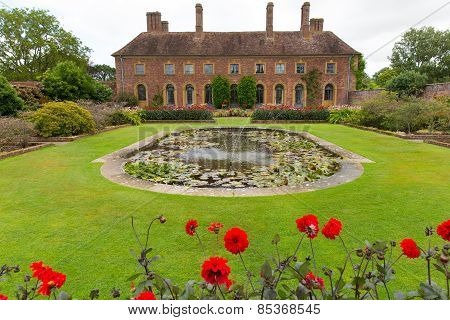 Strode House Barrington Court near Ilminster Somerset England uk with Lily pond and red dahlias
