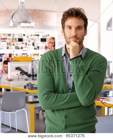 Handsome casual caucasian businessman at business office thinking. Standing, looking at camera, bristly.