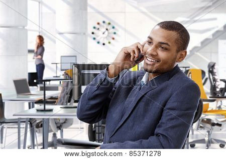 Happy, smiling, successful afro american business advisor talking on mobile phone while sitting at office table, Bright, suit no tie.