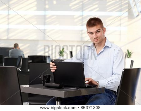 Young casual rookie businessman working on laptop computer at cafe, smirking, copyspace, sitting at table.