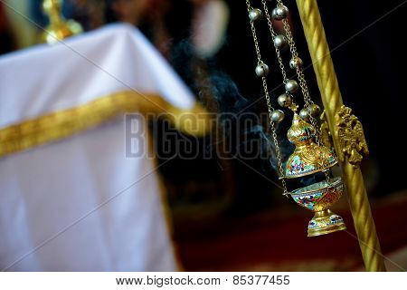 Gold censer hung in the church with side light poster