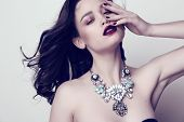 fashion studio photo of beautiful sensual woman with dark hair and bright makeup with luxurious bijou necklace poster