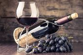 Winery background. Wineglass with bottle of red wine and cluster of grape on wooden table. Toned image poster
