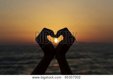 Heart Shape Silhouette Made With Hands Against Sunset