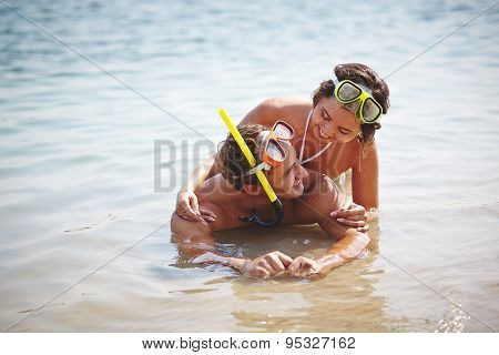 Affectionate couple scuba diving equipment lying in water