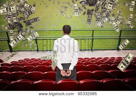 Rear view of young businessman wearing handcuffs against red bleachers looking down on football pitch