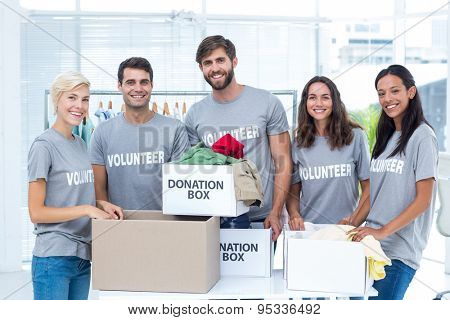 Portrait of happy volunteers friends separating donation stuffs
