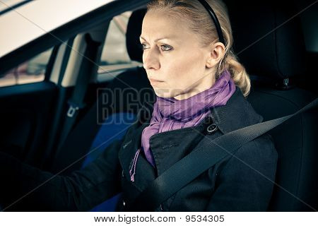 Woman Sitting In Car With Eyes Focused On Road