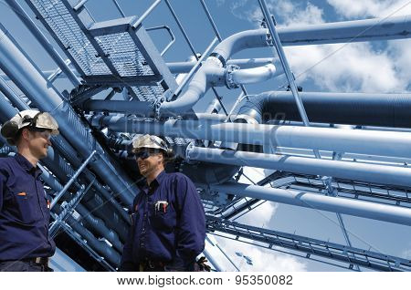 oil and gas workers with refinery pipelines in background