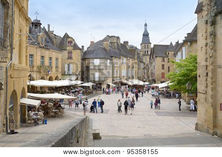 SARLAT, FRANCE - JUNE 28, 2013: Tourist walking in the historic center of old city. Since 2002, the old city of Sarlat included in UNESCO Tentative List