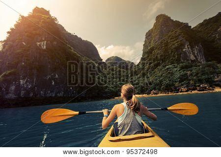 Lady exploring Ha Long Bay (UNESCO World Heritage Site) by kayak. Vietnam