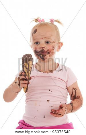 Portrait toddler girl eating chocolate ice cream isolated over white background