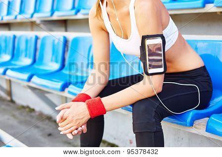Modern girl in activewear sitting at stadium