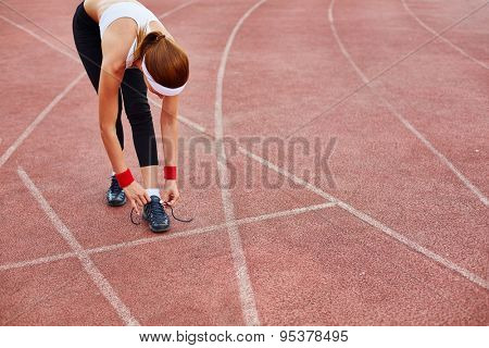 Fit girl in activewear tying her shoelace at stadium