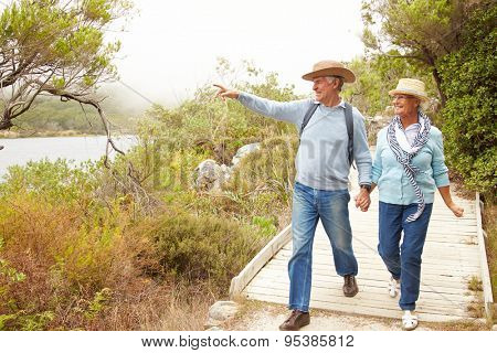 Senior couple walking together by a lake