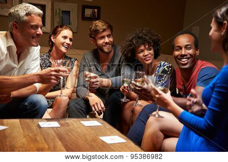 Group of friends sitting around a table at house party