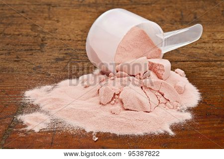 a measuring cup of organic freeze-dried pomegranate fruit powder on a grunge wooden background