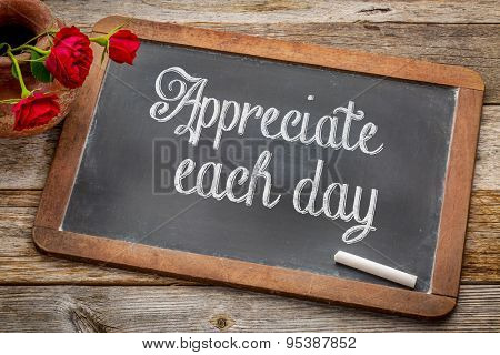 Appreciate each day  - white chalk text on a vintage slate blackboard with red roses against rustic wood