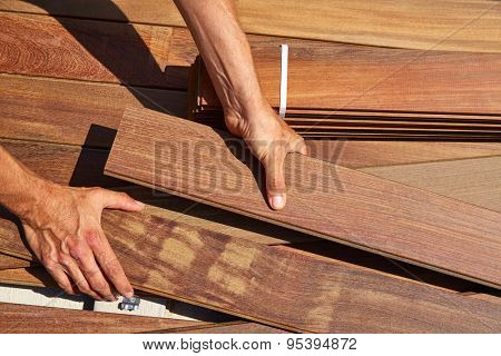 Ipe decking installation with carpenter hands holding tropical wood slats poster