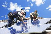 Workers installing alternative energy photo-voltaic solar panels on roof poster
