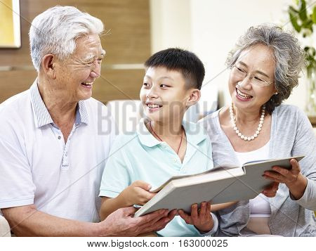 happy asian grandfather and grandmother reading a book with grandson happy and smiling.