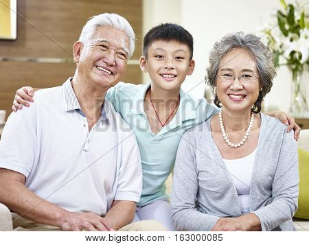portrait of happy asian grandparents and grandson looking at camera smiling.