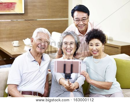 two happy senior asian couples taking a selfie using cellphone on a stick.