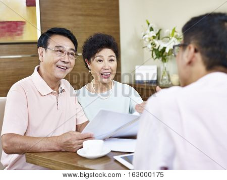 senior asian couple listen to explanation by a sales representative happy and smiling.