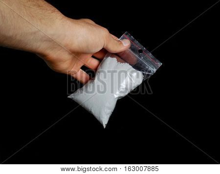 Drug dealer holding bag with cocaine drug powder, men selling drugs junkie on black background
