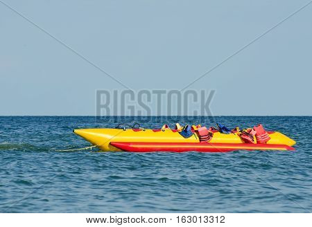 Empty water banana with lifejackets in sea water attraction