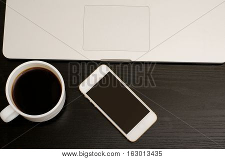 Top view of a smart phone and a cup of coffee near laptop on a black table