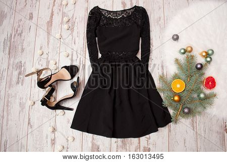 Black dress with lace and black shoes on a wooden background fir-tree branch with ornaments and citrus. fashion concept