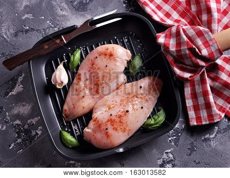 Raw chicken breast with smoked paprika, sea salt and pepper on a cast iron skillet grill.