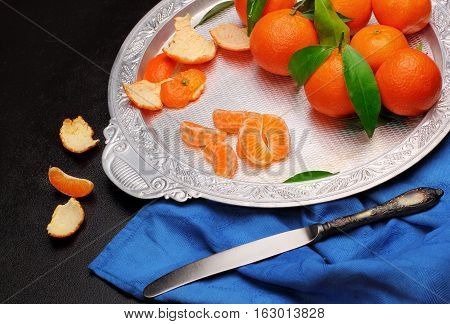 Fresh Tangerine Clementine With Leaves In Silver Tray With Knifeon Dark Stone Background, Top View.c