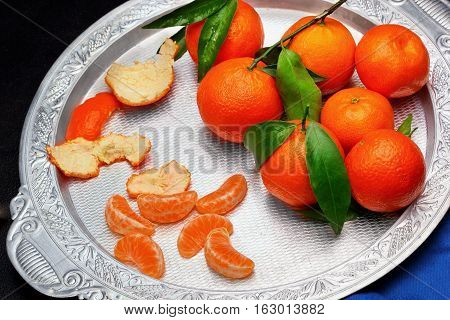 Still Life.fresh Tangerine Clementine With Leaves In Silver Tray On Dark Stone Background, Top View.