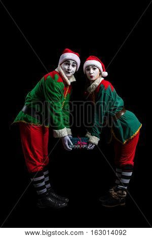 Couple of elf mimes in New Year costumes isolated on black background
