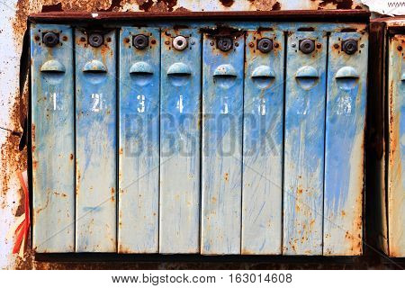 Old metal rusted and numbered mailboxes. Painted blue. Paint partly peeled off.