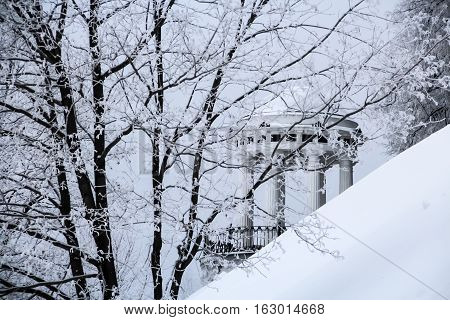 Winter season at Russian city Yaroslavl. Trees with branches covered by frost on foreground. Gazebo and snow-covered slope of the embankment on background. Focus on background gazebo.
