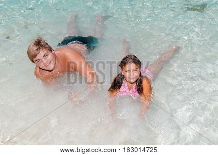 nice amazing gorgeous view of happy joyful kids relaxing near the beach in shallow ocean turquoise water and enjoying their leisure time