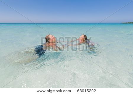 young adolescent and little girl relaxing, swimming and enjoying there leisure time in the ocean