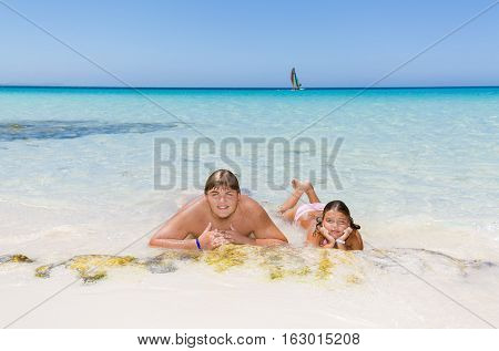 young adolescent and little girl relaxing, swimming and enjoying there leisure time om tropical beautiful beach