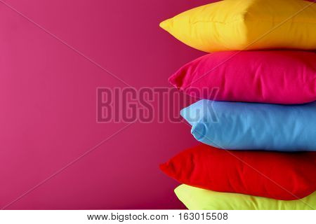 Colorful pillows on a pink background, close up