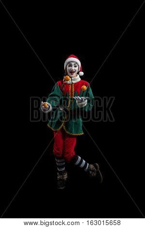 Female mime in New Year costume juggling with mandarines isolated on black background