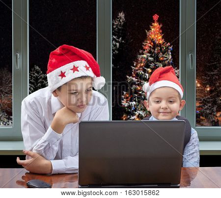 Children in Santa Claus caps looking at a laptop on the background of New Year tree outside the window