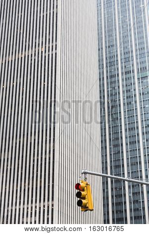 Crosswalk in NYC. Yellow traffic light with a red signal stop on the Manhattan skyline background in New York City USA