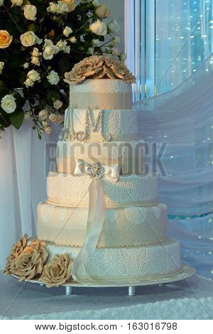 a multi level white wedding cake on a silver base and gold flowers on top