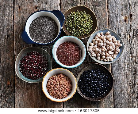 Healthy food - lentils, chickpeas, black beans, red beans, peas, quinoa and chia seeds on old wooden background.
