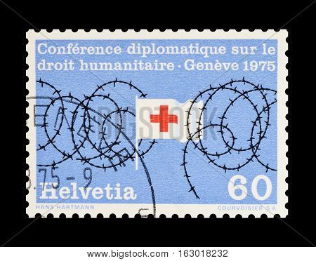 SWITZERLAND - CIRCA 1975 : Cancelled postage stamp printed by Switzerland, that shows Barb wire and a flag.
